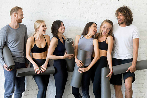 group of healthy young adults holding yoga mats