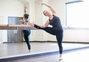Nicole Adams, owner of Origin House of Fitness in Fort Collins, CO doing a stretch at the ballet barre fitness classes